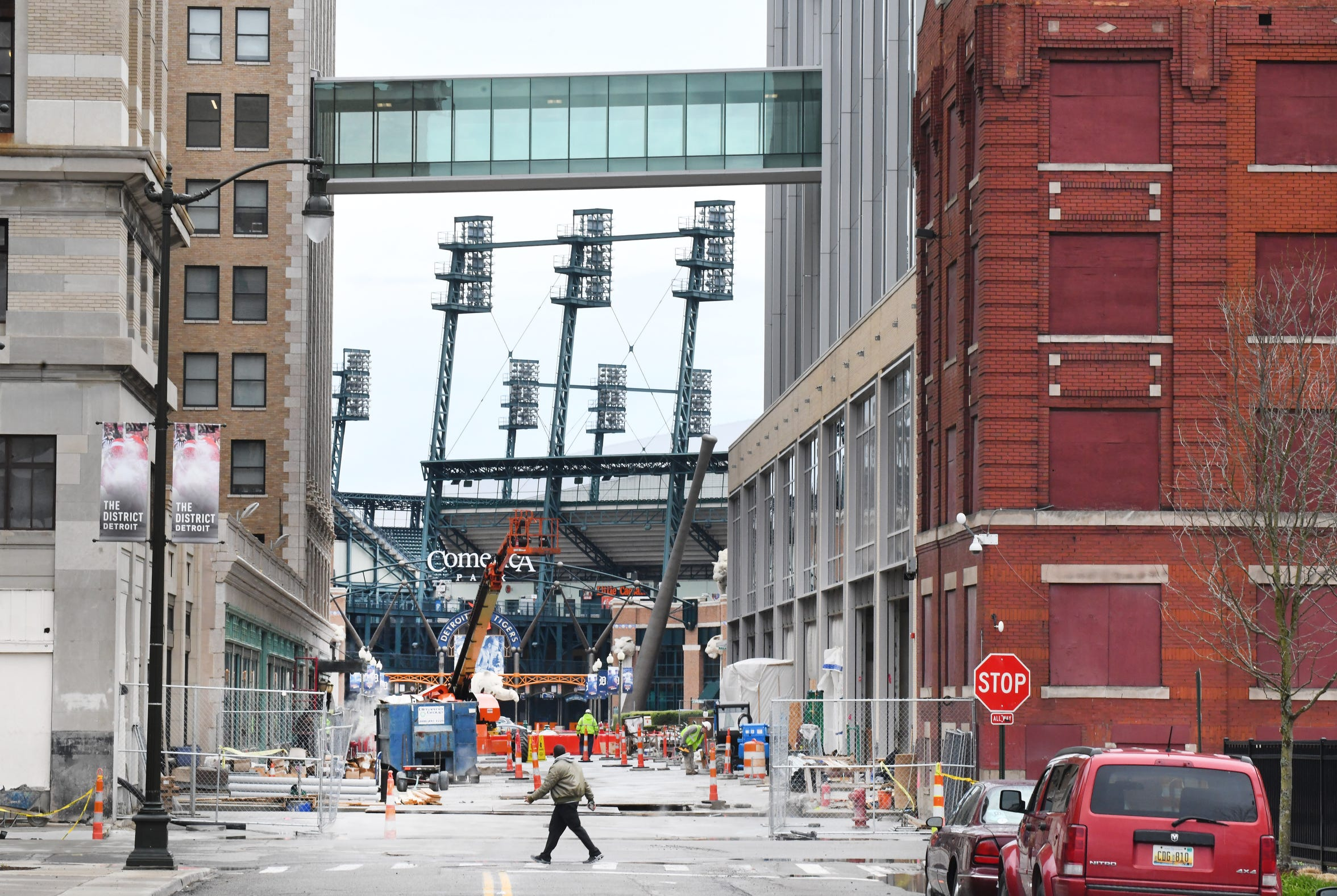 A pedestrian walkway links Fox Theatre and the future Little Caesars headquarters. Comerica Park is in the background. In the foreground are two empty buildings owned by Ilitch-linked entities.