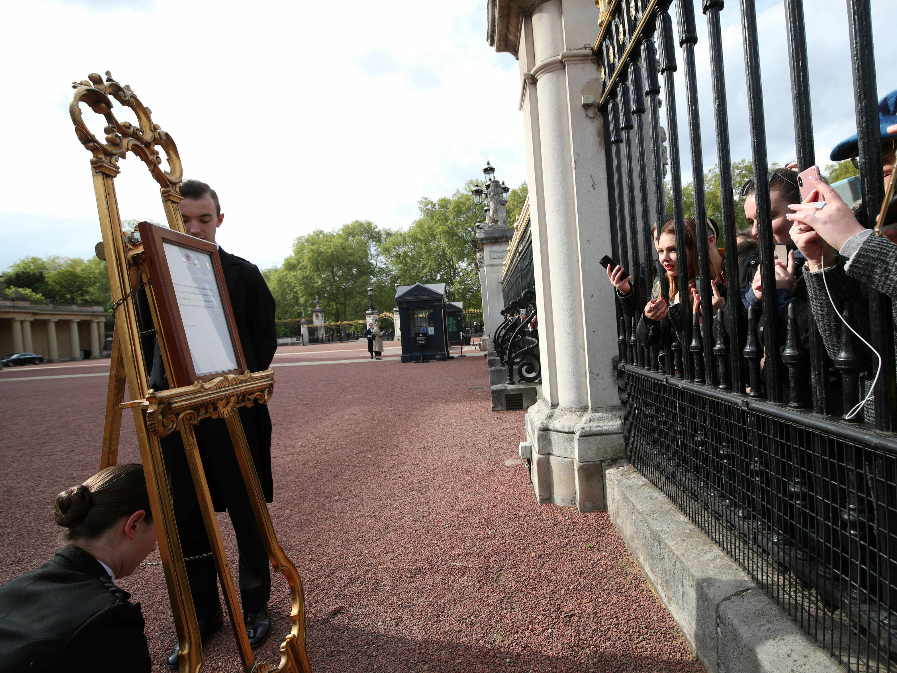 People gather outside the gates of Buckingham Palace to take pictures of the official notice, set on an easel. The official announcement is traditionally placed on public view in the courtyard of the London  palace.
