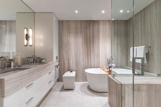 A bathroom made spalike through the addition of basic elements such as candles, bath salts and teak bath caddy.