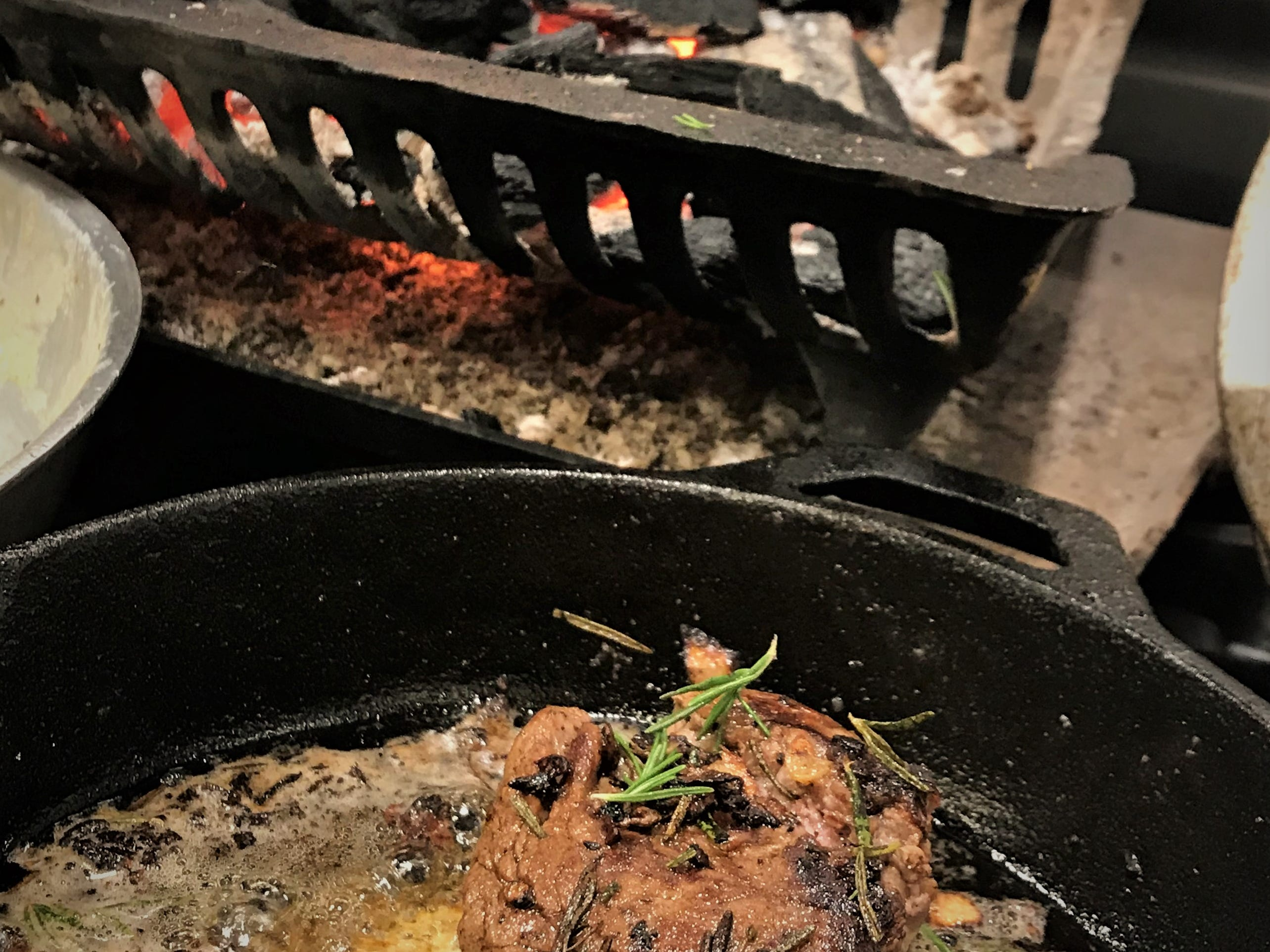 A brazier with wood charcoal is kept flaming all night for cooking Eisenhower ribeyes right on the coals at Amy's on Franklin. In front, a cast-iron seared filet mignon with rosemary and butter.