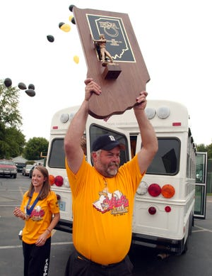 Mike Wilson, coach of the ISHAA State 3A Softball Championship team, the Boonville High School Lady Pioneers, holds the trophy high as he and the team arrive back home to the schools parking lot that was full of cheering fans Sunday, June 11, 2006.