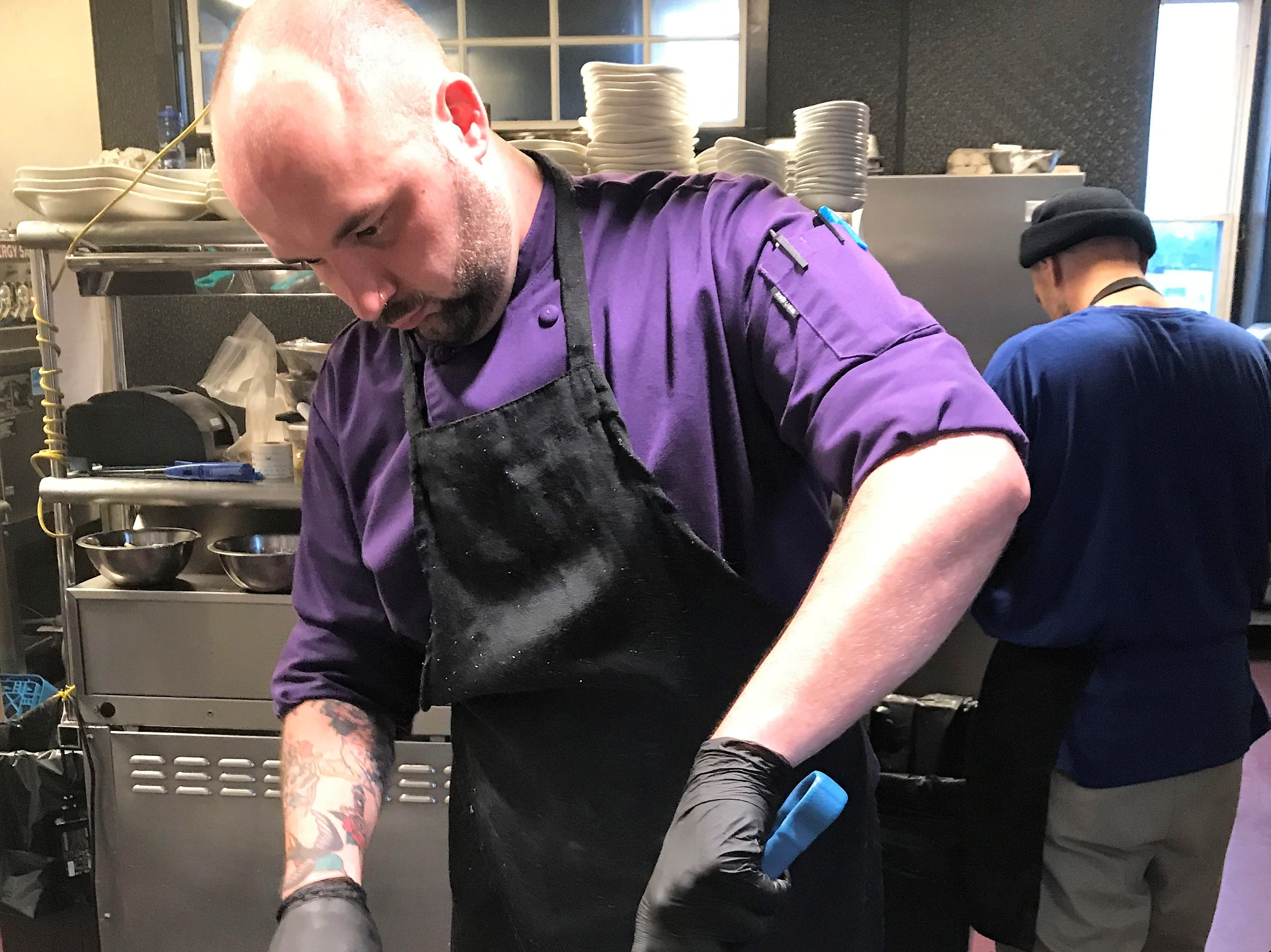 Chef Jeremiah Galey slices a grilled chicken breast at Amy's on Franklin.