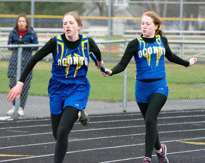 Alaina Edgar and Emmy Reed complete a handoff in the 4x200m relay at the Oconto JV Invitational on April 30.