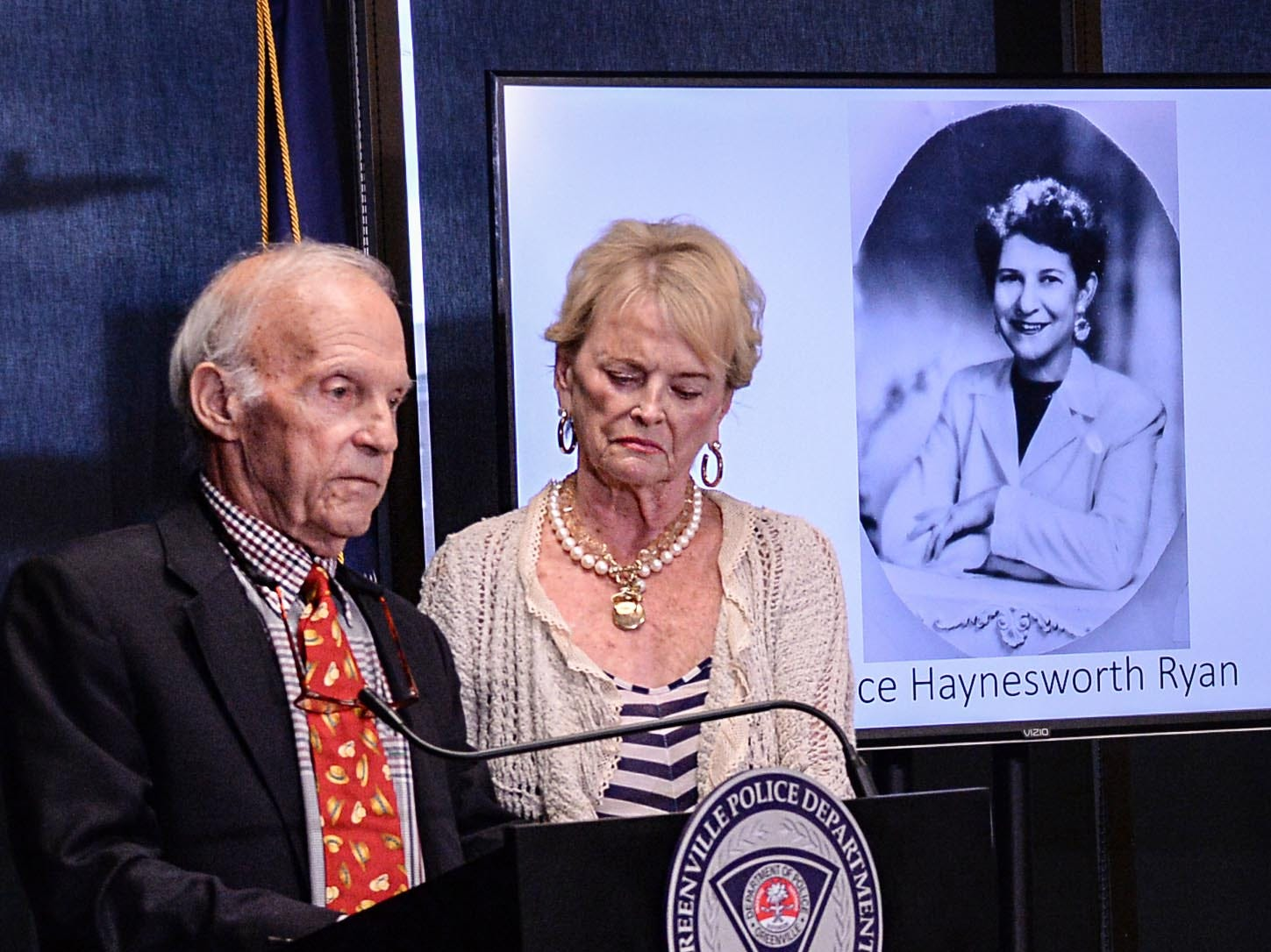 Joe Ryan, left, of Greenville stands with his wife near a photo of his late mother Alice Haynesworth Ryan, during a city police announcement of an arrest in the 1988 cold case homicide in Greenville Monday. Police arrested suspect Brian Keith Munns.
