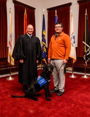 Judge Greg Pinski poses with military veteran Fernando Terrones and his new service dog, Major, on Monday afternoon at the Cascade County Courthouse.  Terrones is a participant in Veterans Treatment Court with Judge Pinksi and was accepted into a collaborative program between Carroll College's anthrozoology department and Dog Tag Buddies that will provide him with instruction on living with a service dog.