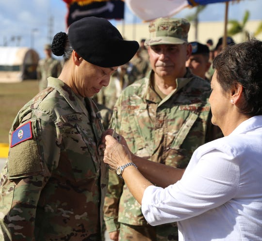 Governor Lou Leon Guerrero, Commander-In-Chief of the Guam National Guard, at right, pins 2- star ranks on Esther J.C. Aguigui, at left, making her a Major General on Guam, during a Retreat Ceremony, witnessed by Guam Guard Airmen, Soldiers, guests and family members, on Sunday, May 5, at the GUNG's Readiness Center in Barrigada.