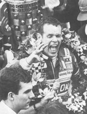 Bobby Unser shouts for joy in Victory Lane with the wreath of orchids around his shoulders and the Borg-Warner trophy behind him on May 24, 1981.