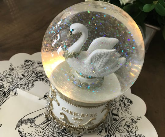 """Glitter spins around a gilded swan to the tune of """"Castle On A Cloud"""" from """"Les Miserables"""" in Cake Bake Shop's snow globes, which may center holiday tables at the Carmel location opening in 2019."""