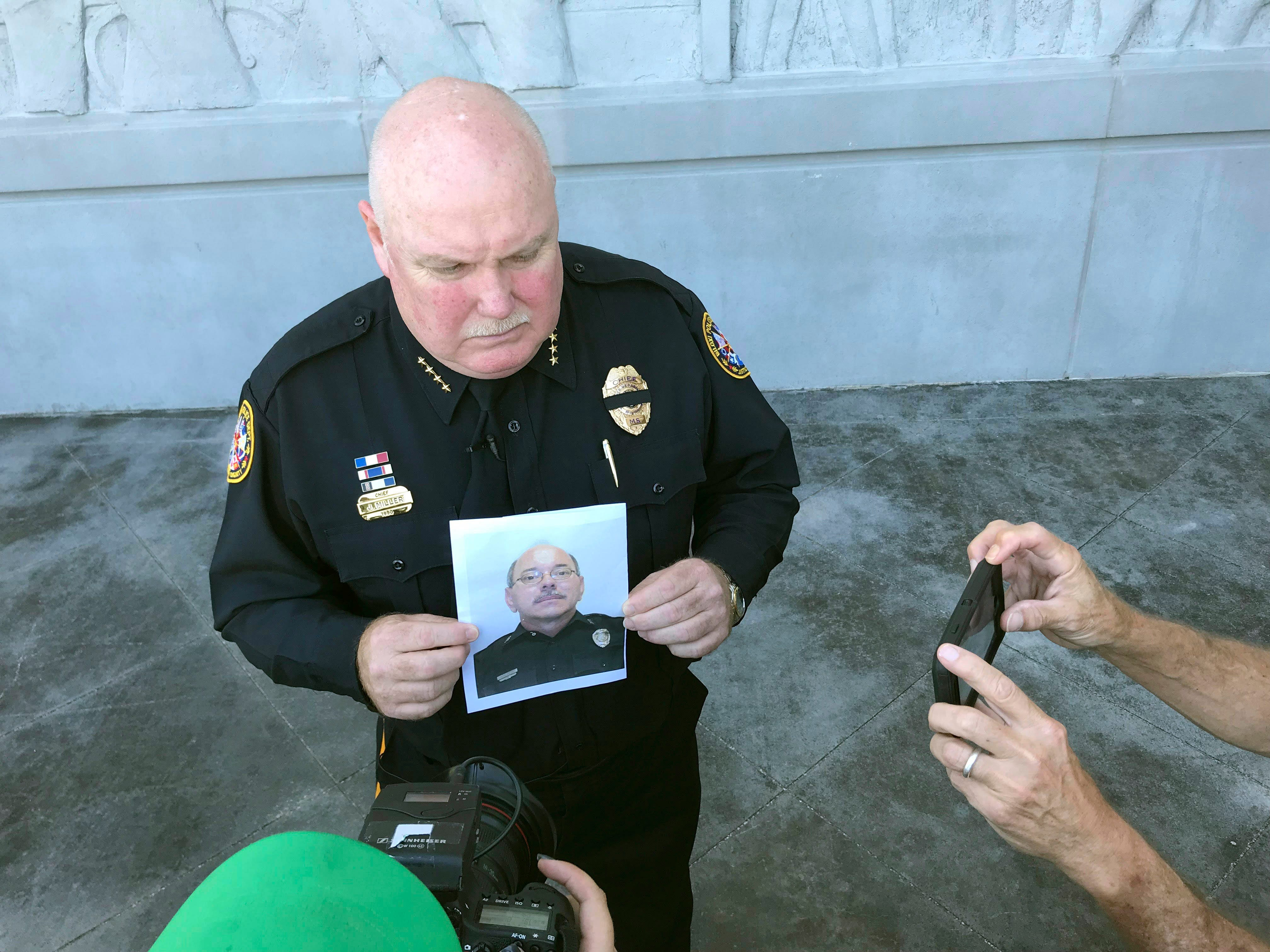 Biloxi Police Chief John Miller holds a departmental photograph of Officer John McKeithen who was killed Sunday night, May, 5, to media, outside the department building, in Biloxi, Miss., prior to a news conference Monday, May 6, 2019.