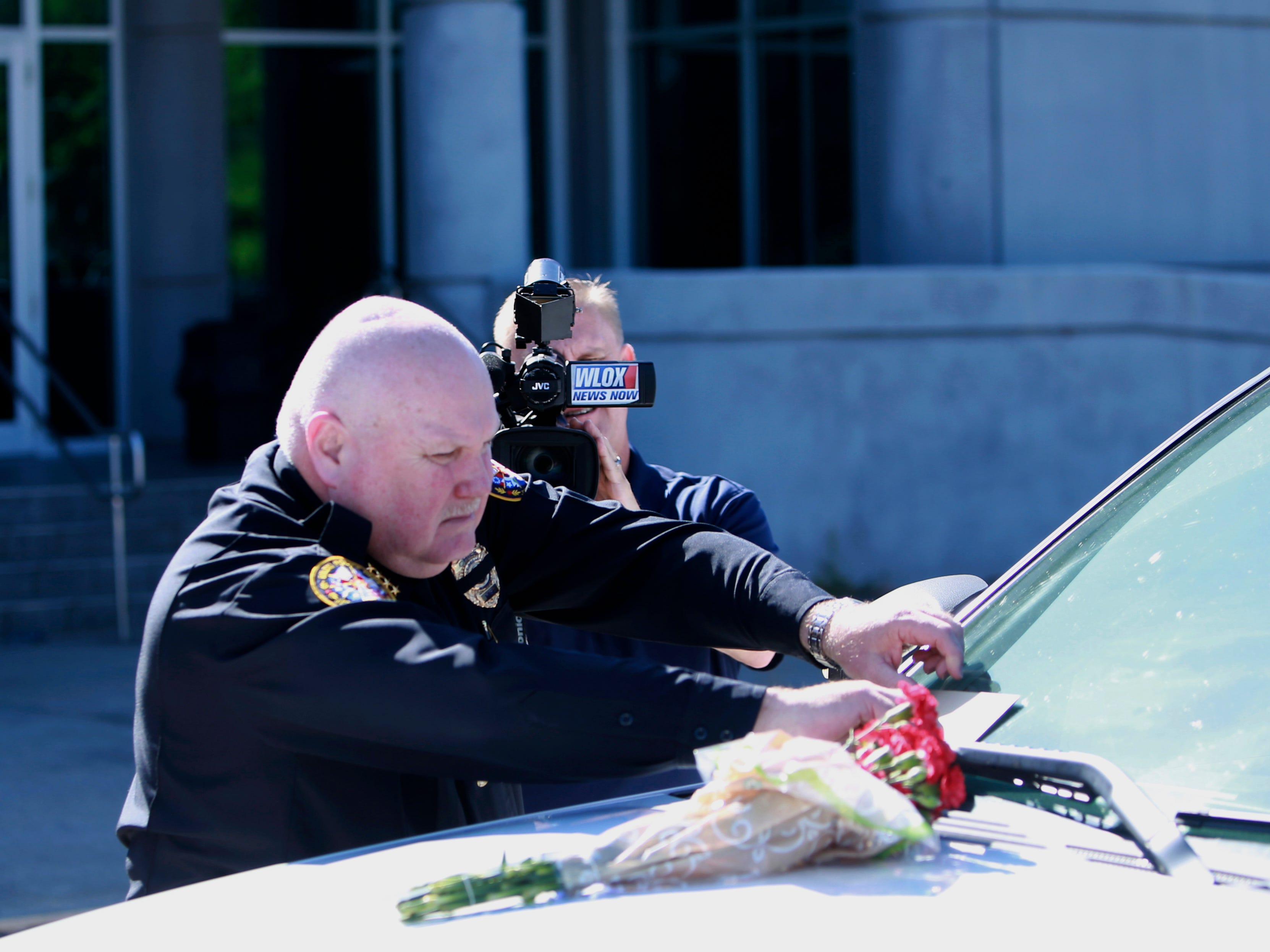 Biloxi Police Chief John Miller places flowers and a card on the police SUV of Officer Robert McKeithen, outside the station in Biloxi, Miss., Monday, May 6, 2019. McKeithen was killed in the line of duty outside the Biloxi Police Department, Sunday night. A manhunt is underway to find the suspect, who shot McKeithen multiple times, police say.
