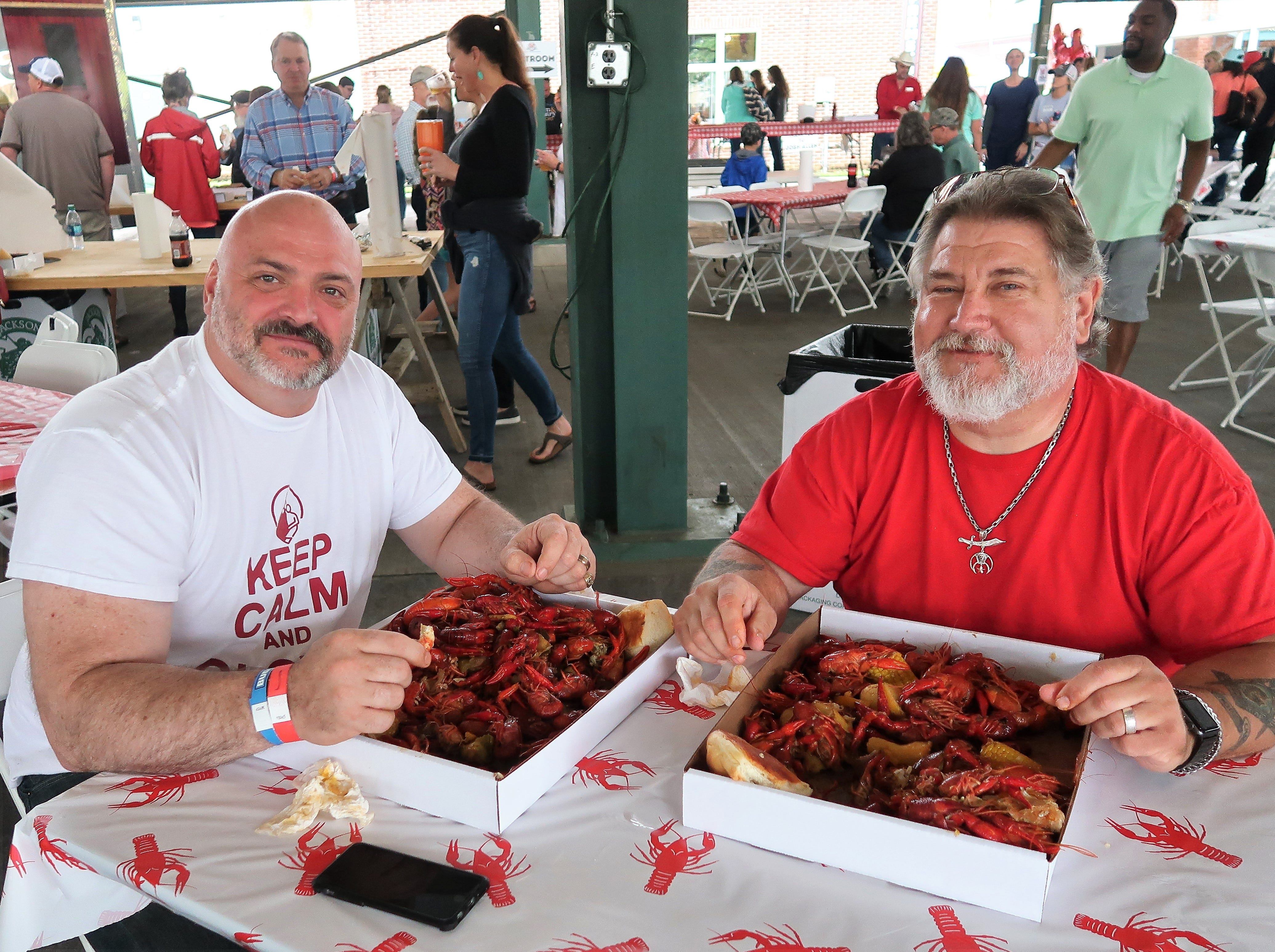 David Vince and Kemo Jackson sit down with their platters of crawfish at the Second Annual Crawfest fundraiser for the Scarlet Rope Project at the West Tennessee Farmer's Market in Jackson on May 4, 2019.