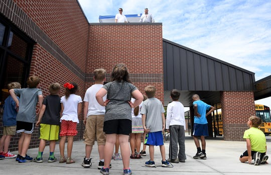 South Gibson County Elementary School students look up at their principal and superintendent Billy Carey and Eddie Pruett on the roof of their school, Monday, May 6. Carey and Pruett told students if they reached their fund raising goal for St. Jude, they would sleep on the roof for one night.