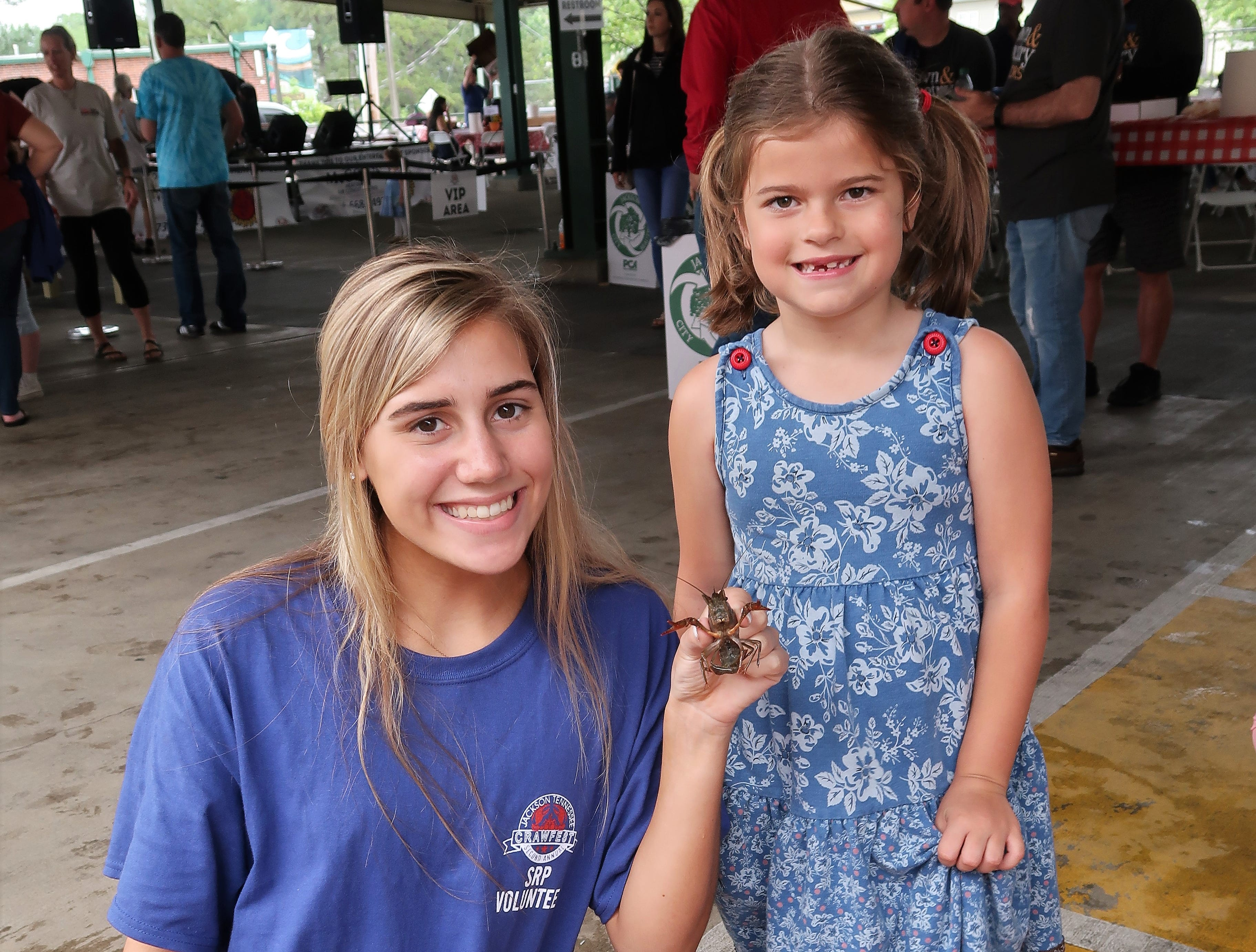 A volunteer and a child pose with a crawfish at the Second Annual Crawfest fundraiser for the Scarlet Rope Project at the West Tennessee Farmer's Market in Jackson on May 4, 2019.