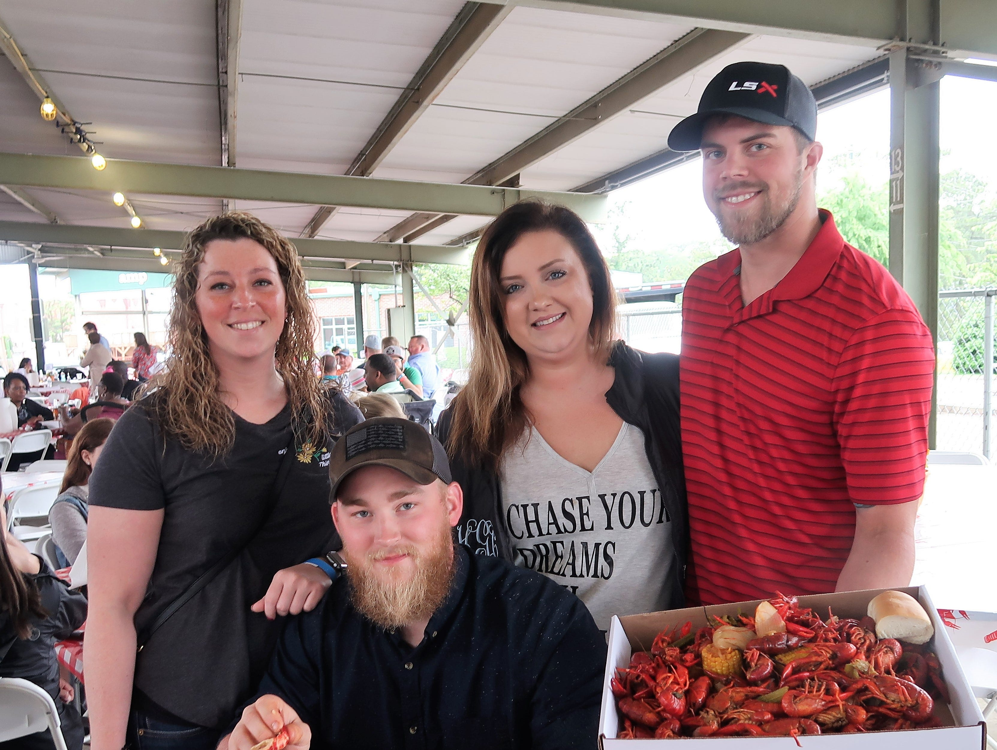 Shenise Cannasta, John Dodd, Heather G. and Jason Maitland display their boxes of crawfish at the Second Annual Crawfest fundraiser for the Scarlet Rope Project at the West Tennessee Farmer's Market in Jackson on May 4, 2019.