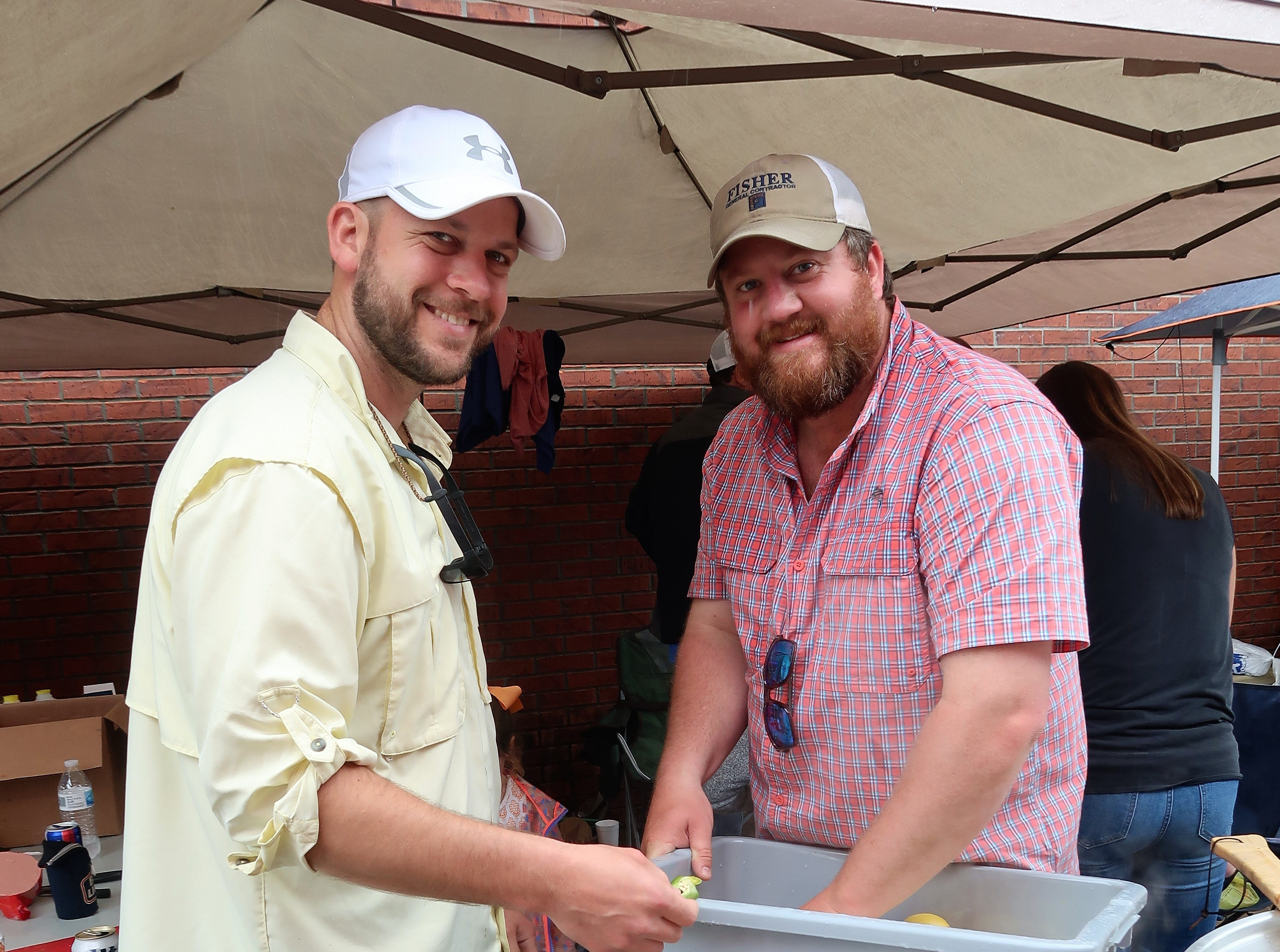 Eric and David, members of a crawfish cookteam, add some celery to their crawfish boil at the Second Annual Crawfest fundraiser for the Scarlet Rope Project at the West Tennessee Farmer's Market in Jackson on May 4, 2019.