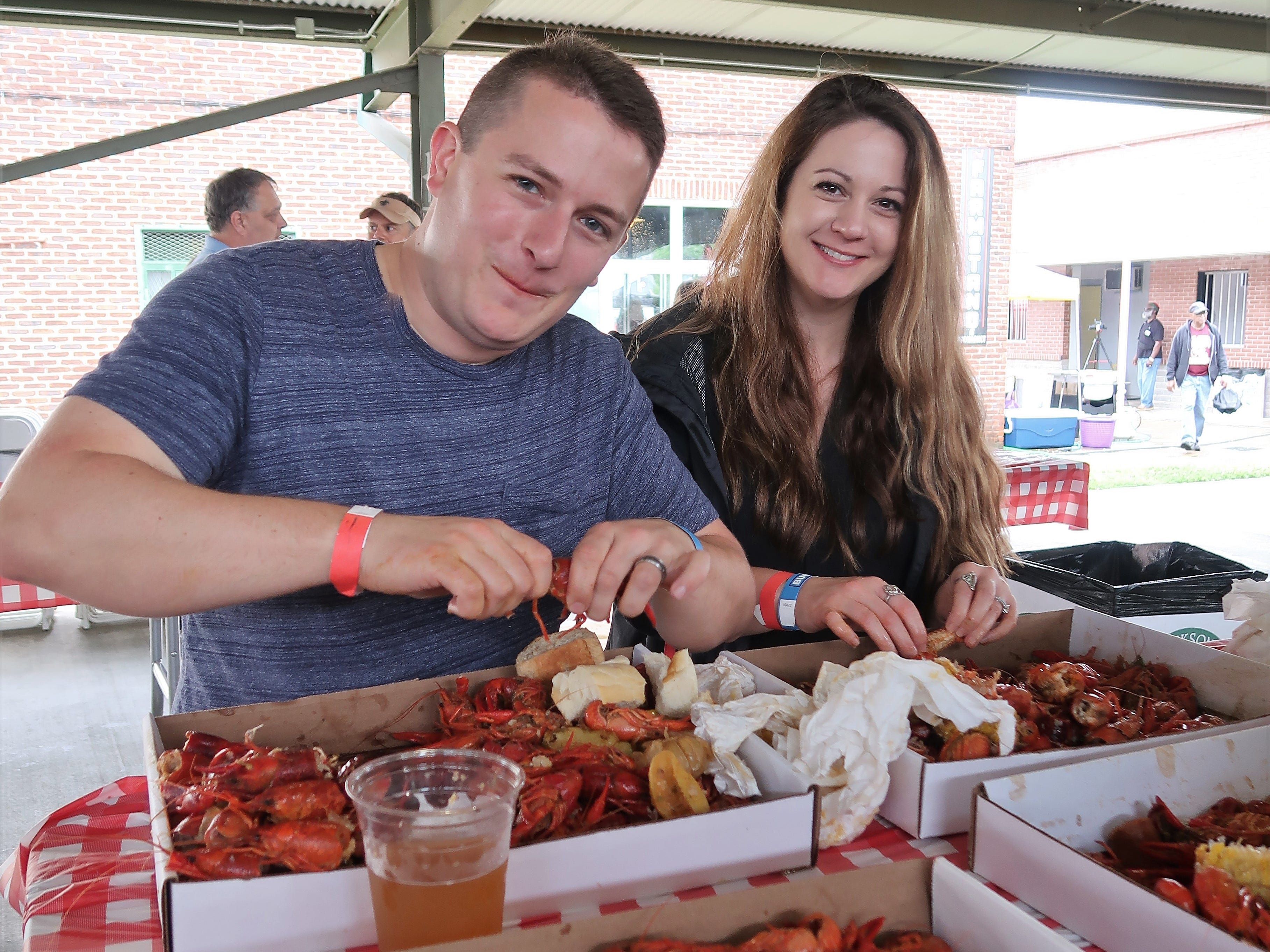 Andren Meehan and Jessica Meehan dig into their baskets of crawfish at the Second Annual Crawfest fundraiser for the Scarlet Rope Project at the West Tennessee Farmer's Market in Jackson on May 4, 2019.