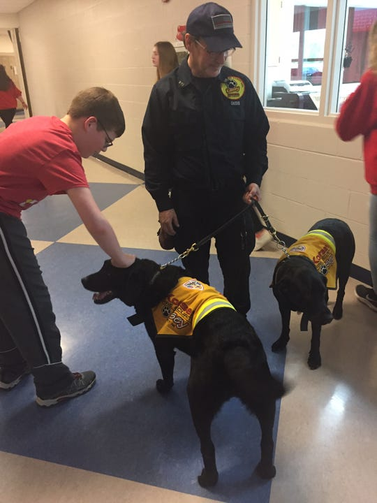 A Liberty Union Middle School student pets one of the two Labradors instructor Jeff Owens used Monday as part of Koorsen Fire & Security's fire safety program at the middle and elementary schools.