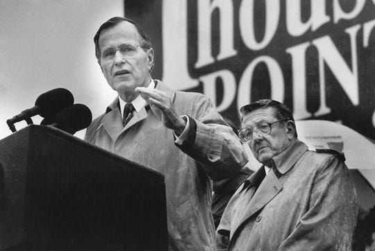 President George H.W. Bush addresses a rain-drenched crowd at 495 Union Ave. on Nov. 23, 1989. Lionel Linder, editor of The Commercial Appeal, is at right.