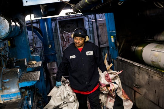 Gerald Smith cleans up newspapers around the presses inside of the Commercial Appeal's press room before the start of a run of Saturday's newspaper on April 7, 2017.