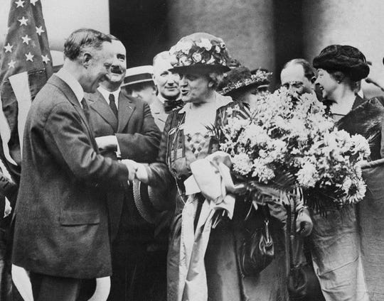 Former Governor of New York Alfred E. Smith, welcomes Carrie Chapman Catt, women's suffrage leader, on her triumphal return from Tennessee, the last state to ratify the 19th Amendment giving women the right to vote, in New York, Aug. 27, 1920. Miss Catt carries a bouquet of blue and yellow flowers, colors of the National American Woman's Suffrage Association. (AP Photo)