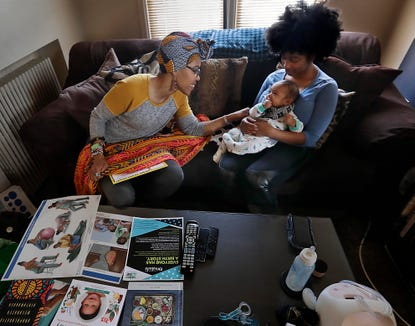 Vanessa Johnson, a doula and nurse, meets with client Natasha Lettner and her son for a post-delivery consultation.