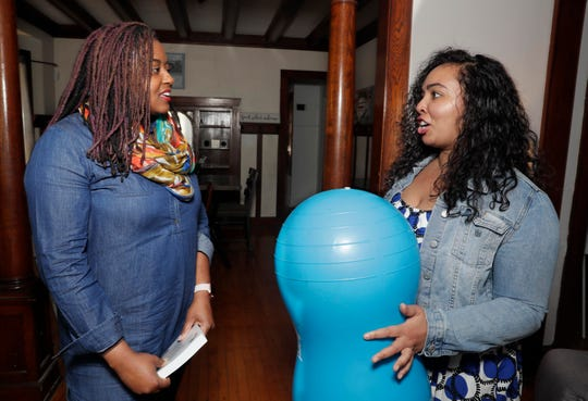 "Infant mental health consultant Kisha Shanks (left) and doula Shani Toor talk about how a ""peanut ball"" can be used to provide comfort to moms during pregnancy and in labor."