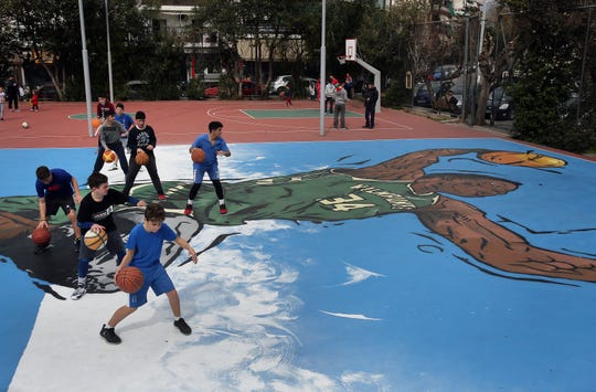 Locals play basketball on a court covered in a large piece of urban art or graffiti showing Greek NBA All-Star game player Giannis Antetokounmpo going for a slam dunk, at his neighborhood of Sepolia, Athens, Greece. The graffiti was created by artist Same84 in the open basketball field of Triton in the area of Sepolia, where the 22 year old Milwaukee Bucks forward Giannis Antetokounmpo, known as the 'Greek Freak', grew up in poverty and made his first steps into the sport of basketball at the age of 12.  EPA/SIMELA PANTZARTZI