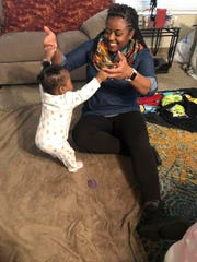 Infant mental health consultant Kisha Shanks plays with a baby while meeting with a client to determine the infant's development progress.
