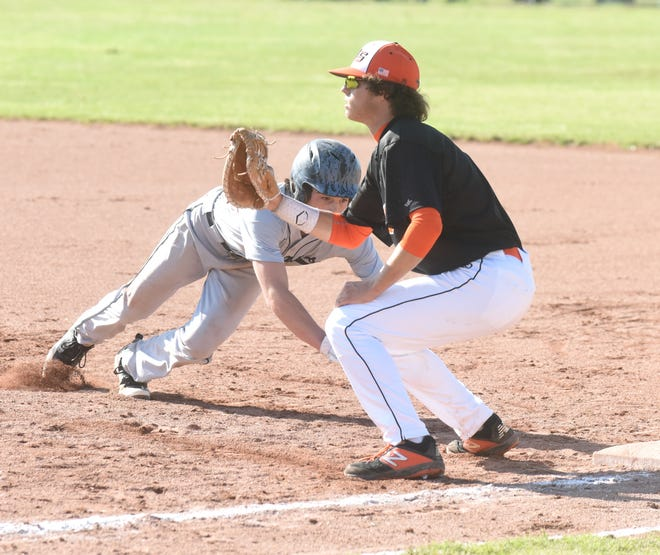 Izard County's Coby Everett dives back to first base as Viola's Dalton Roork awaits the throw on Sunday evening.