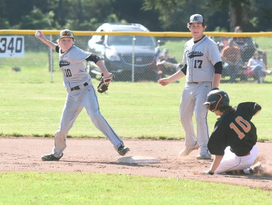 Izard County shortstop Noah Everett throws to first as Viola's Gage Harris slides into second.