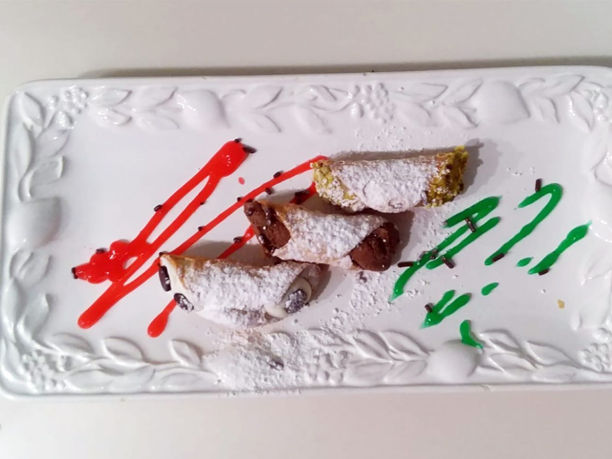 A cannoli sampler dessert plate features three differet fillings: chocolate, ricotta cheese and pastry cream.