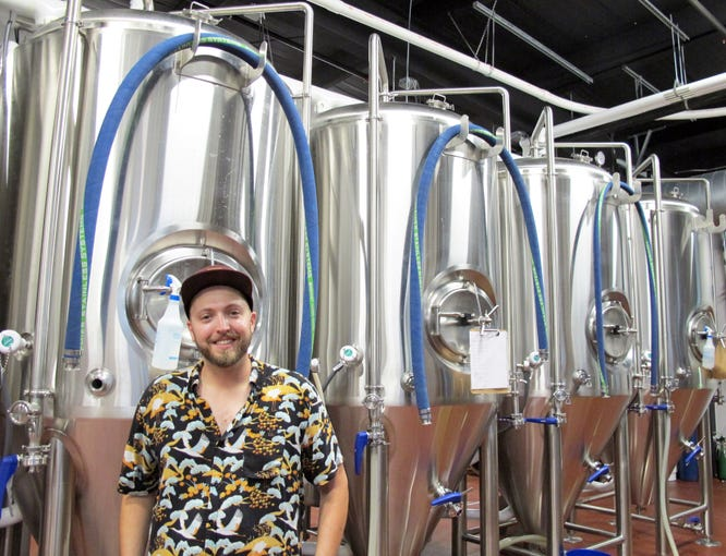 Ankrolab Brewing Co. owner Adam Kelley pauses a moment by fermentation tanks in his new brewery on its opening day, Friday, May 3, 2019, on Bayshore Drive in East Naples.