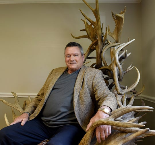 "Jim Wade, owner of Wade Cattle Company and Ohio Pro Bucks in Pataskala, sits in the ""trophy chair"" made of elk, moose, and deer antlers from all over the country. Hunters who visit the hunting preserve frequently are photographed in the chair to commemorate their trip."