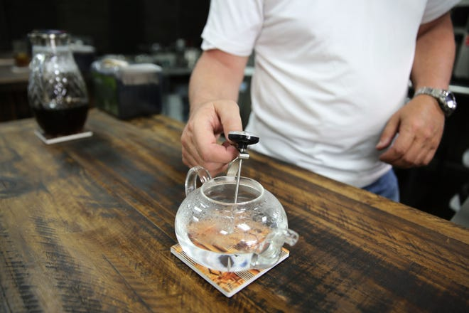 Cafecito Divino co-owner Mike Fry checks the temperature while preparing a pot of flowering tea at Cafecito Divino on Tuesday, April 30, 2019.