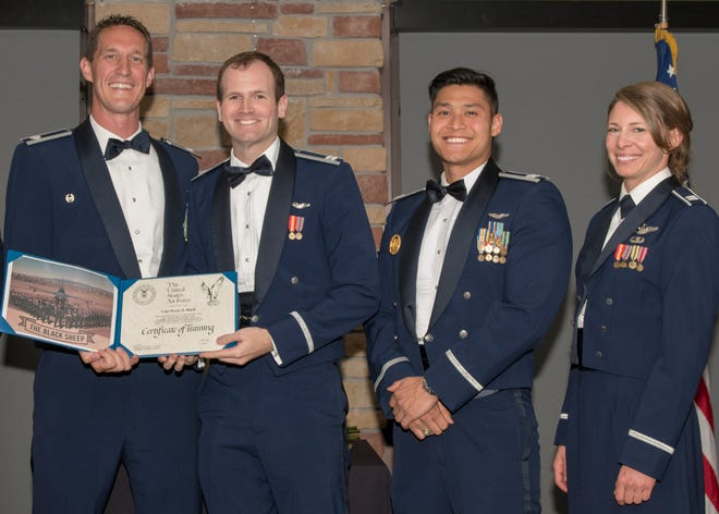 Lt. Col. Mark Sletten, 8th Fighter Squadron commander, presents Capt. Reese Black, 8th FS F-16 Basic Course graduate, with a certificate of training, May 4, 2019, at Club Holloman on Holloman Air Force Base, N.M. Eight Viper pilot students graduated from the 8th FS first F-16 B-Course, nearly eighty years since the squadron's induction on Nov. 20, 1940.