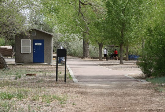 Community members walk on the trail in Berg Park East on Monday.