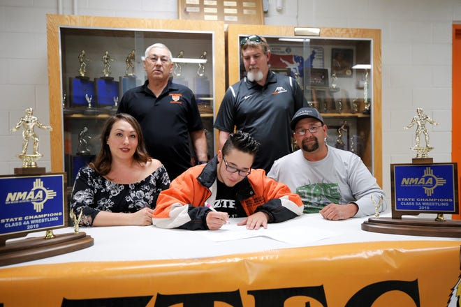 Aztec's Hunter Medina, who won an individual state title this past season, signs his National Letter of Intent on Monday to continue his wrestling career at New Mexico Highlands University.