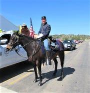 Matthew Midgett rides Belle as flag bearer for the annual Smokey Bear Days parade in Capitan.