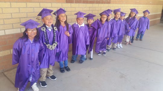 Students in the Pre-K classes of Paula  Romero and Allison Barcus walk to their graduation ceremony.