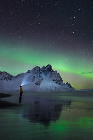 Troy Cini captured this stunning image of the northern lights in Iceland, with his friend Austin Ashley framed against the Vestrahorn mountain while standing on the Stokknes beach. The photo has been entered in a National Geographic contest.