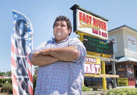 Owner James Dabney stands near one of his feather signs outside of East River Smokehouse in Navarre on Monday.