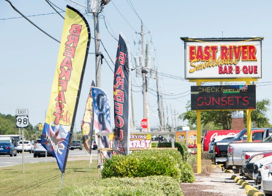 Feather signs are seen outside of East River Smokehouse in Navarre on Monday.