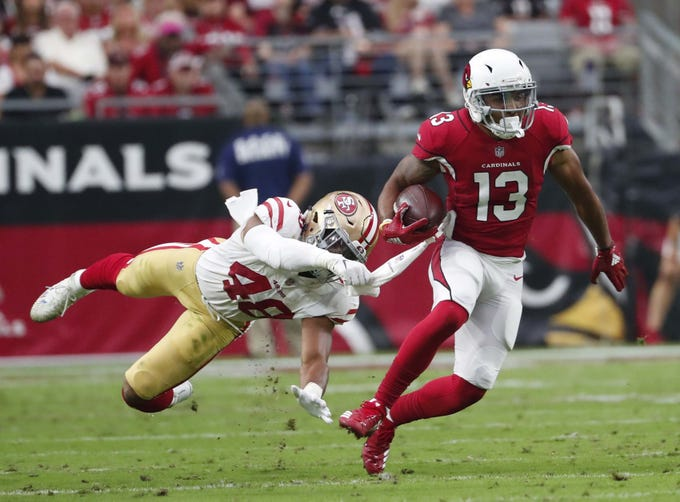 Cardinals receiver Christian Kirk escapes a tackle by 49ers linebacker Fred Warner after a catch In the second quarter of a games against San Francisco on Oct. 28 at State Farm Stadium.