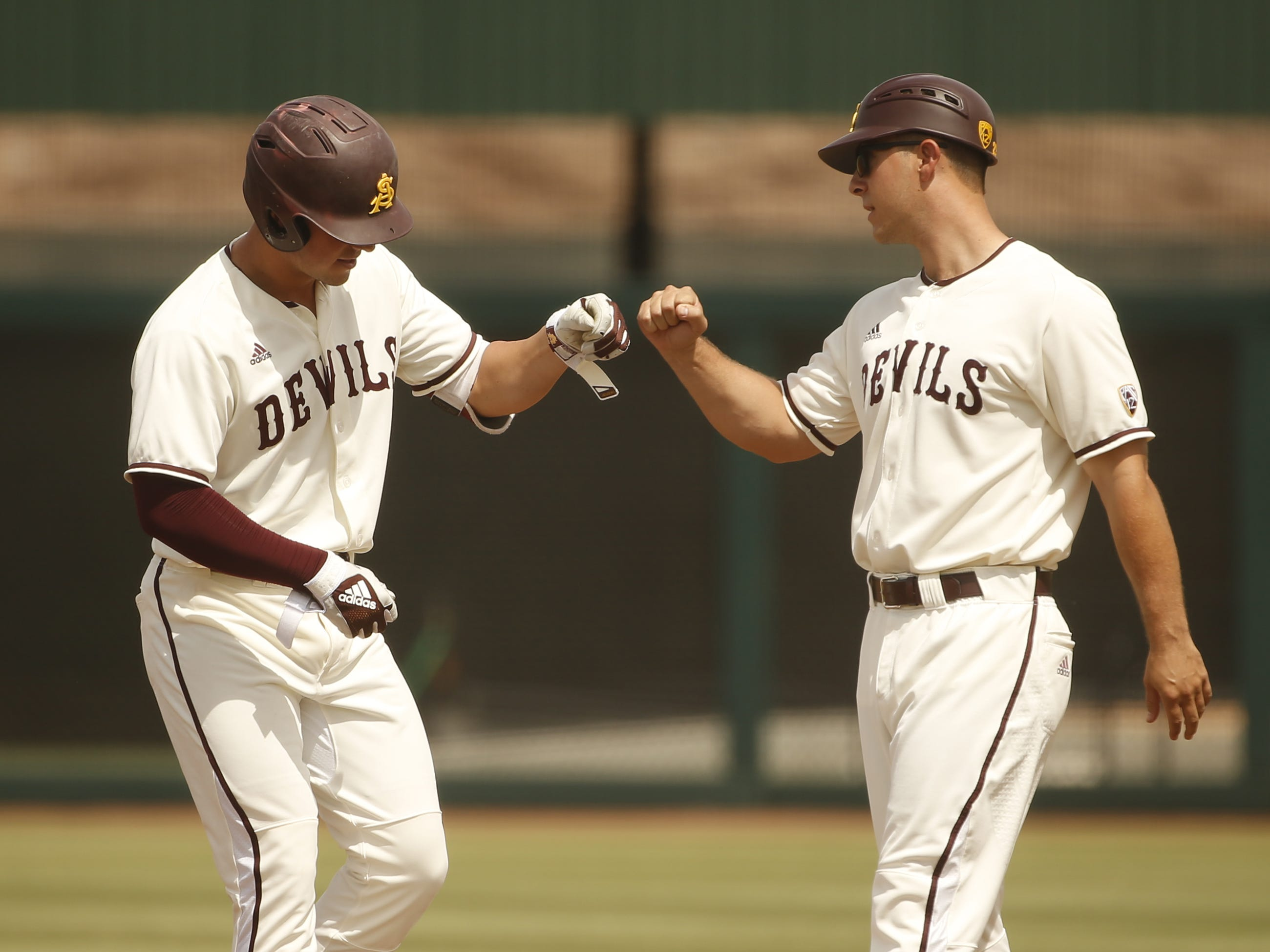 ASU's Spencer Torkelson (20) bumps fist with his first base coach during the first inning against UCLA at Phoenix Municipal Stadium in Phoenix, Ariz. on May 5, 2019.