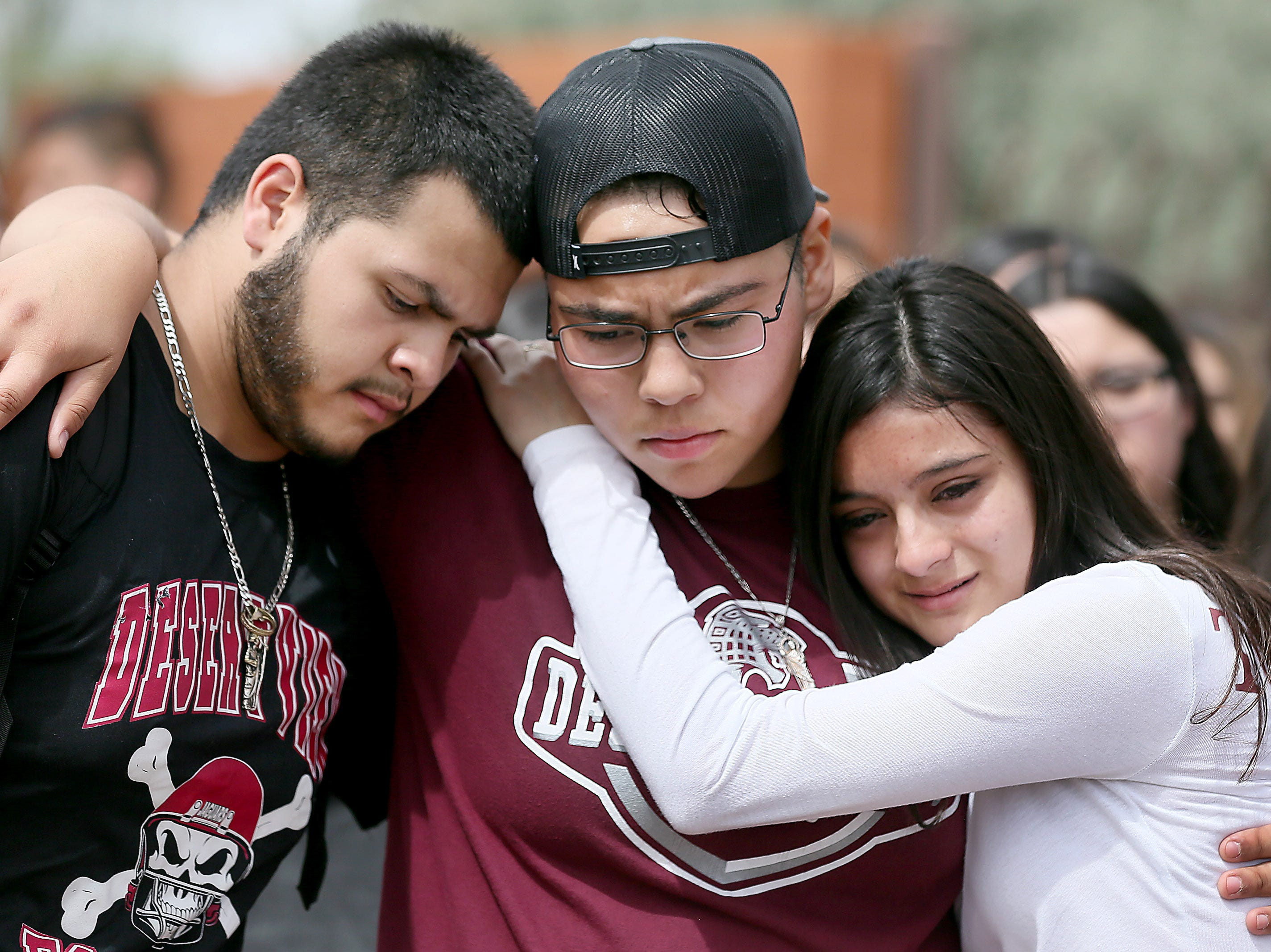 (From left to right) Marcell Ibarra, 18, Daffne Anselmo, 16, and Jamilet Fragoso, 16, comfort each other after talking about their close friend Thomas Torres, a Desert View High School student who was taken into custody by  Border Patrol after a traffic stop by a Pima County Sheriff's Department deputy on May 2 in Tucson, Ariz.