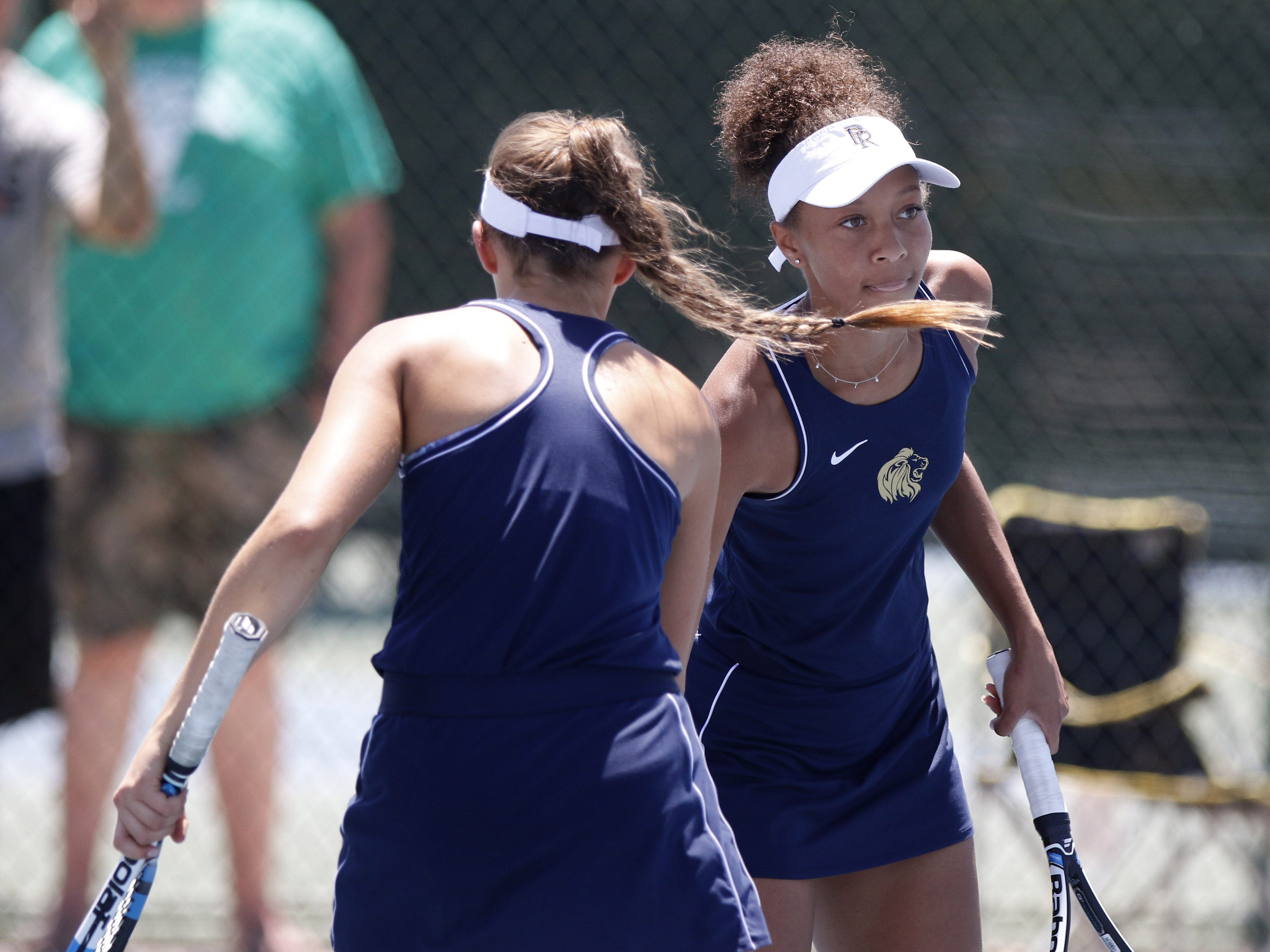 Pusch Ridge's Regan Harris and Sofia Fetsis low-five each other after winning a point against Thatcher during the Division III tennis team state championship in Glendale, Arizona, May 04, 2019.