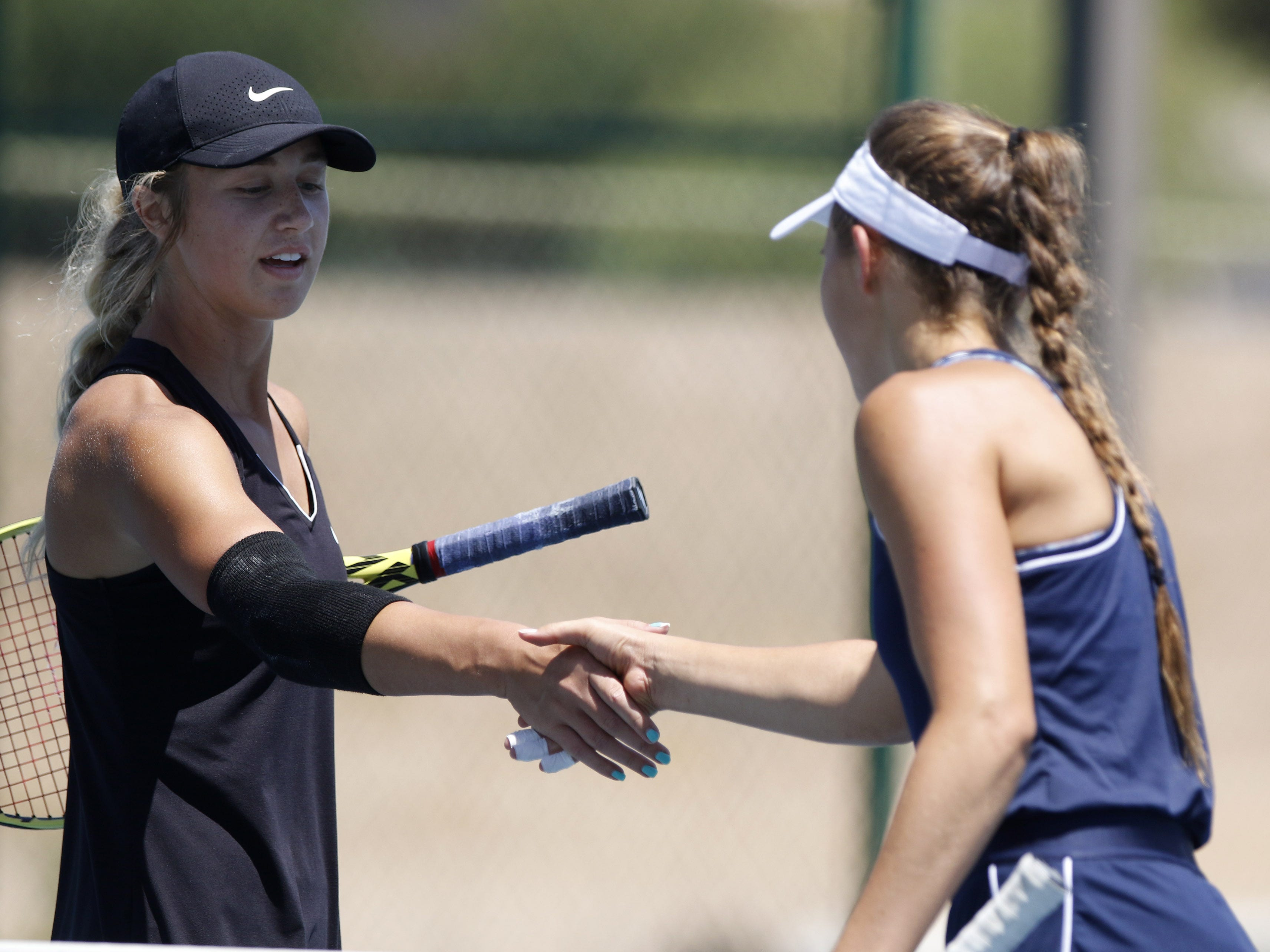 Thatcher's Lacie Whitmer shakes hands with Pusch Ridge's Sofia Fetsis after their match during the Division III tennis team state championship in Glendale, Arizona, May 04, 2019.
