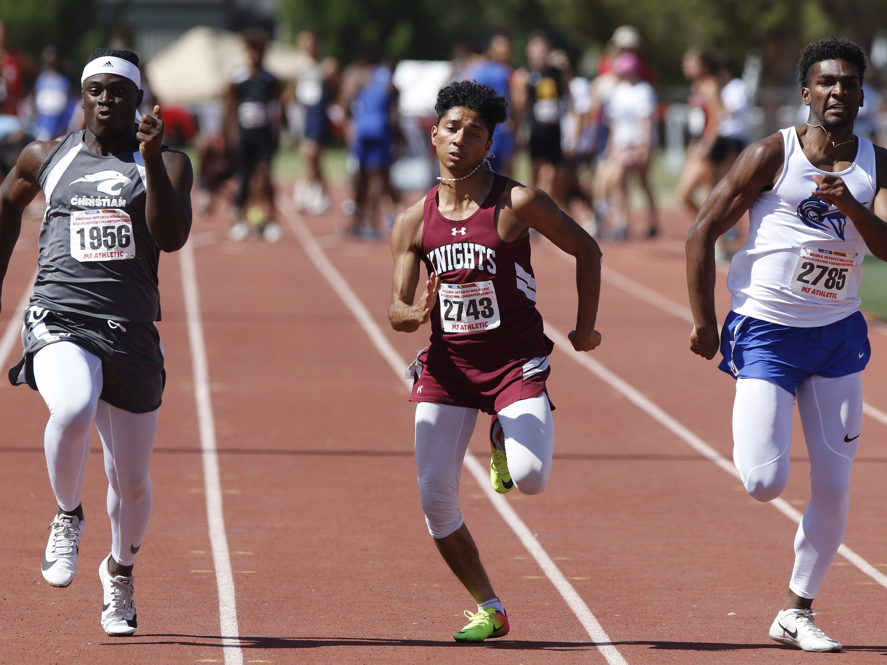 Phoenix Christian's Manace Freeman, Arizona Lutheran's Jacob Holquin and Valley Christian's Jalen Grijalva sprint down the stretch during the Division III 100 meters championship during the 2019 Arizona State Track and Field Championship at Mesa Community College in Mesa, Arizona, May 04, 2019.
