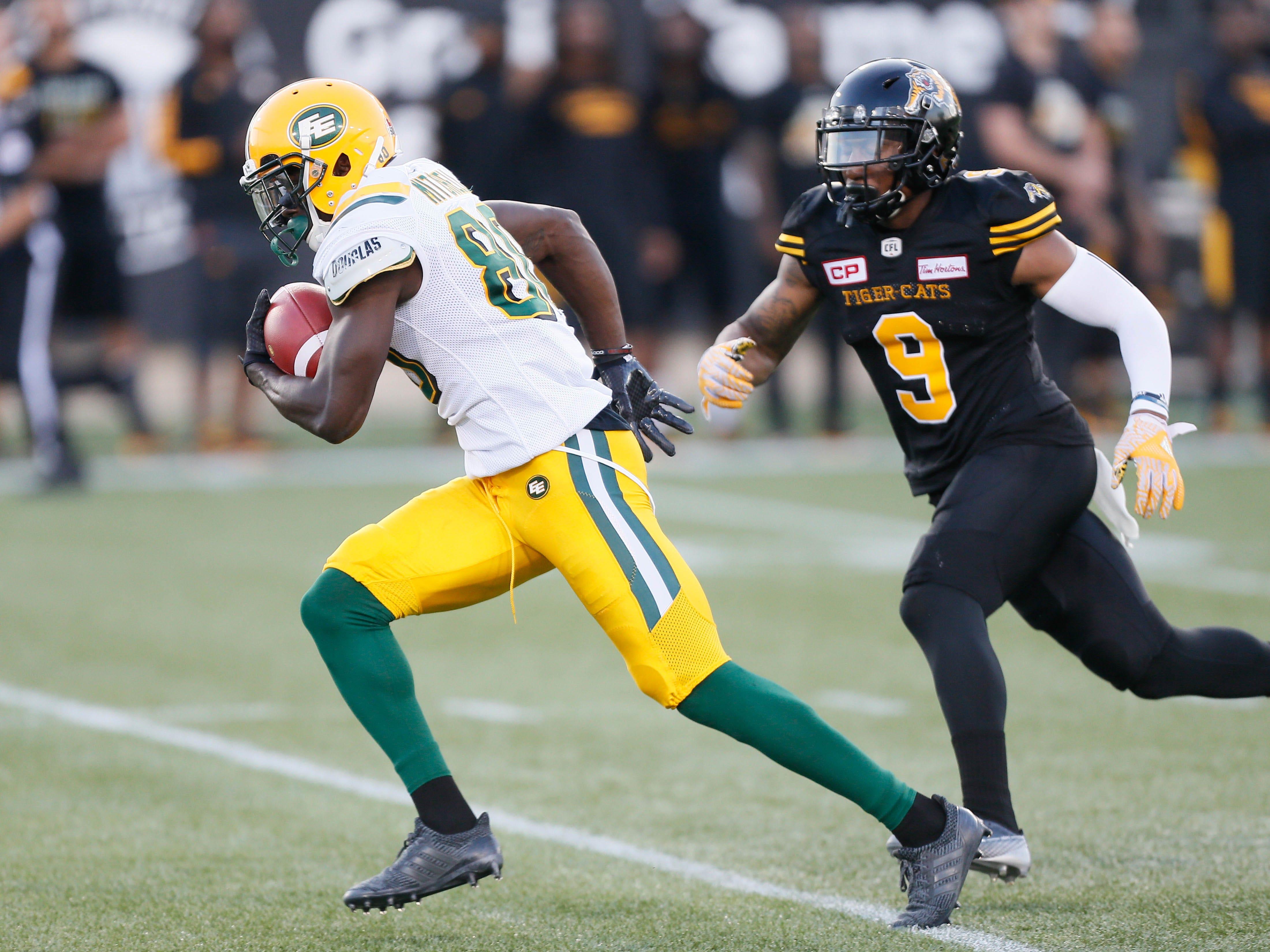Edmonton Eskimos receiver Bryant Mitchell runs past Hamilton defensive back Khalid Wooten to score a touchdown at Tim Hortons Field.