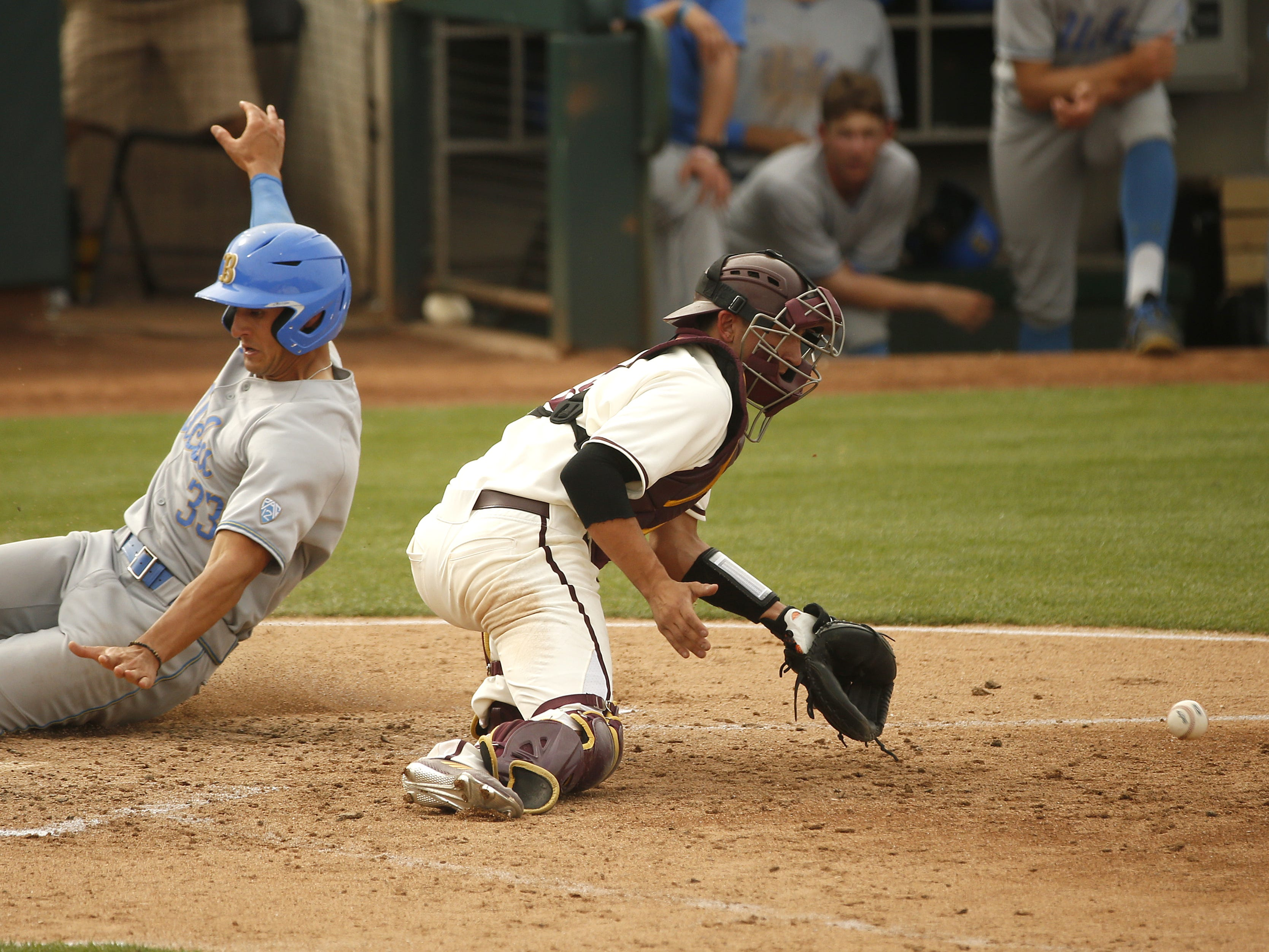 UCLA's Chase Strumpf (33) slides safely home past a late throw to ASU's Sam Ferri (9) during the sixth inning at Phoenix Municipal Stadium in Phoenix, Ariz. on May 5, 2019.